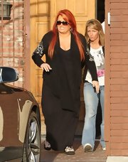 Wynonna Judd paired a long black cardigan with silver sleeve embellishments with a long black dress for a casual daytime look.