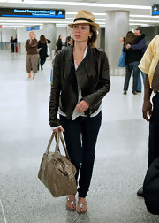 Dannie Minogue hit the airport carrying a shimmery nude oversized tote bag.