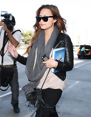 Demi Lovato gave her airport style a rocker chick vibe with a leather jacket and studded cellphone case.