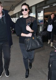 Demi Lovato arrived on a flight at LAX wearing a black Christopher Kane sweatshirt with patent and lace accents.