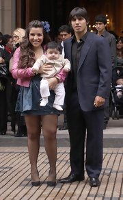 Kun wears a classic blue pinstripe suit in Buenos Aires with his wife and baby.