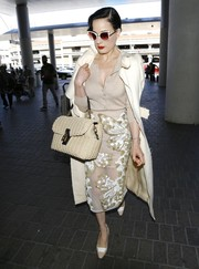 Dita Von Teese completed her ultra-stylish travel outfit with a butterfly-embellished pencil skirt.