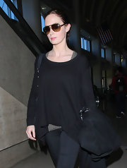 Emily Blunt layered her travel look, wearing a black tunic sweater over a charcoal tank.