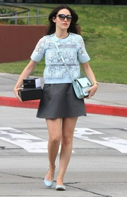 Emmy Rossum visited the Pacific Design sweater wearing a white lace blouse over a gray dress.
