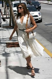 Eva looked bright and beautiful in a flowing white sundress with a two-toned leather shoulder bag.