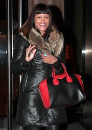 Eve was snug and stylish in a black down coat with a fur collar as she left the Trump Soho Hotel.