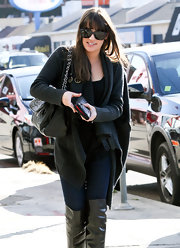 Lea Michelle added luxe appeal to her cozy street look with a black chain strap purse.