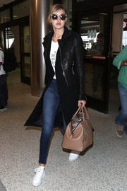 Gigi Hadid landed at LAX looking tough-chic in a black RtA leather jacket layered over a long vest.