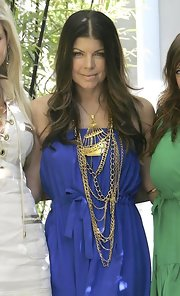 "Fergie mixes of the ""3D Ghostship Necklace"" with a bunch of gold chains. This bold accessory looks great against her periwinkle ensemble."