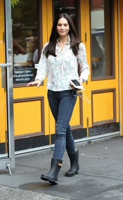 Genesis Rodriguez kept her feet protected with a pair of black rain boots.