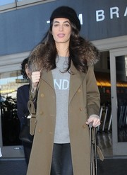 Amal Clooney touched down at LAX looking chic in a black wool ivy cap and a tan fur-collar coat.