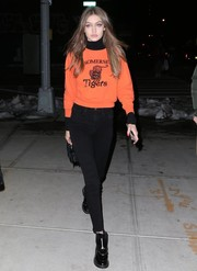 Gigi Hadid stayed comfy in an orange sweater and black jeans while out in New York City.