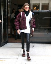 Gigi Hadid looked super toasty in her layered look, consisting of a purple Vetements jacket, a white hoodie, and a black turtleneck, while out during Fashion Week.