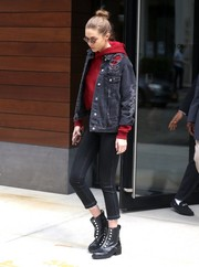 Gigi Hadid went grunge-chic in a torn denim jacket layered over a red hoodie while out and about in New York City.