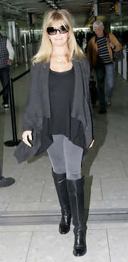 Goldie Hawn kept things in the same color family at Heathrow, layering a charcoal open front cardigan over a black tunic.