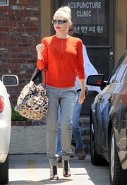 Gwen Stefani chose a pair of gray slim-fit slacks to team with her sweater.