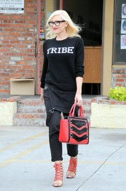 Gwen Stefani finished off her look with an extra splash of red via a military-inspired leather tote.