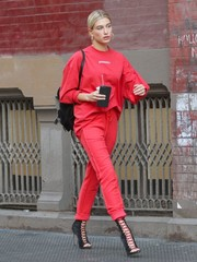 Hailey Baldwin matched her top with a pair of red track pants by Danielle Guizio.