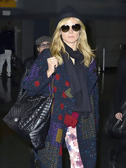 Heidi Klum paired her eclectic travel attire with a chic black leather quilted tote.