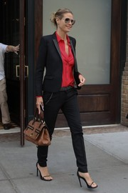 Heidi Klum looked perfectly put together in a black stripe-detail pantsuit teamed with a red button-down while out and about in New York City.