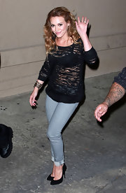 Hilary wears a sheer black tee with light skinny jeans and black pumps.