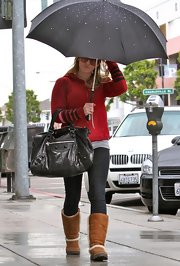 "Hilary dressed down for a rainy day and carried the black leather ""Arena Giant Work"" tote bag. This style is very popular in the young Hollywood crowd because it can be dressed up or down and is easily paired with most looks."