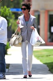 Janice Dickinson teamed her polished street attire with a bone leather tote with braided handles.
