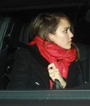Jessica Alba accessorized with a bright red scarf by Love Quotes for a pop of color to her black coat.