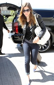While hoping a flight at LAX airport Jessica toted around a white handbag.