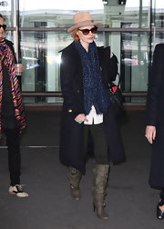 Jessica Chastain bundled up in a black wool coat and olive green knee-high boots.
