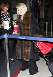 Joan lugs a suitcase at the airport in a fur trimmed coat.