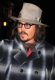 Johnny paired his plaid over coat with a sleek fedora hat.