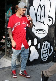 Justin Bieber teamed his top with faded blue jeans.