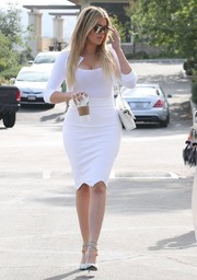 Khloe Kardashian looked sweet in a cropped white Alaia cardigan layered over a tight top while attending Easter service.