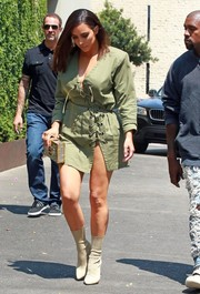 Kim Kardashian was spotted out in West Hollywood wearing an army-green lace-up mini dress with a dangerously high slit.