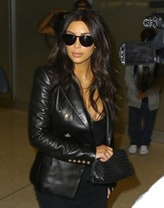 Kim Kardashian hid her eyes behind a pair of Kardashian Kollection shades as she faced paparazzi in Miami.