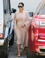 Kim Kardashian sheathed her baby bump in a tight nude dress teamed with an elegant pink coat for a day out in Hollywood.