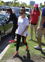Kourtney Kardashian made her gym sneaks pop with those bright orange laces.