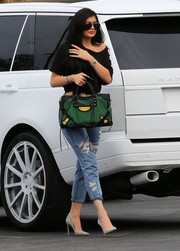 For her arm candy, Kylie Jenner chose a sporty green, yellow, and black canvas and neoprene tote by Balenciaga.