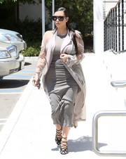 Kim Kardashian cut a stylish figure in a gray Haider Ackermann silk-mousseline trenchcoat  layered over a body-con dress while filming in Agoura Hills.