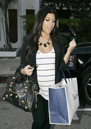 "Kourtney's wearing the super popular ""Black Resin Triangle Necklace"" from Nicole Richie's line of jewely. Kim has the same one. Maybe Kourt raided her closet!"