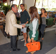"Kourtney's bright orange Hermes ""Kelly"" bag injected her look with a playful sense of style."
