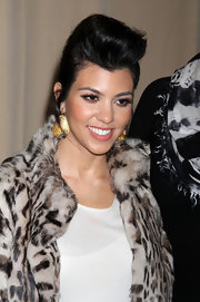Kourtney Kardashian added a little glitz to her leopard fur coat with golden dangle earrings. Her look was completed with a sleek pompadour and wispy lashes.
