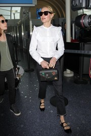 Kate Bosworth went old school in a long-sleeve white ruffle blouse while catching a flight.