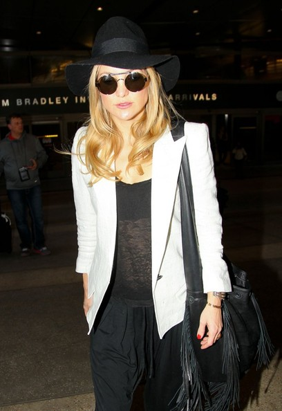 Kate Hudson accessorized with a floppy black hat for her flight.