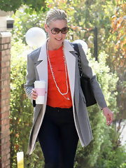 Katherine Heigl added a pop of color to her gray and white dual layered coat with a ruffled orange top.