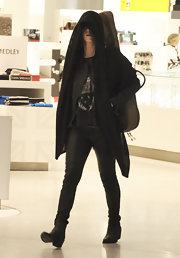 Katy Perry traveled in a loose graphic tee and black ankle boots.