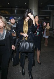 Kendall Jenner bundled up in a black wool coat for a flight to LAX.