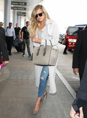 Khloe Kardashian bundled up in a pale-gray Malene Birger trenchcoat for a flight out of LAX.