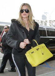 Khloe Kardashian accessorized with a pair of sporty aviators for a flight.